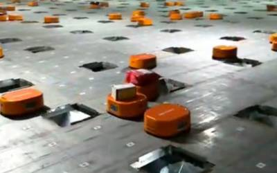 WHO NEEDS HUMANS? Incredible video shows army of orange self-charging robots which sort 200,000 packages a DAY in a Chinese warehouse