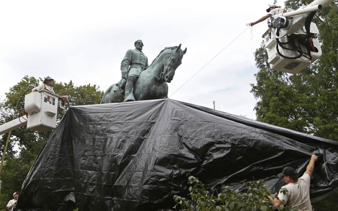 TARPS COVERING CONFEDERATE STATUES ARE BEING RIPPED DOWN